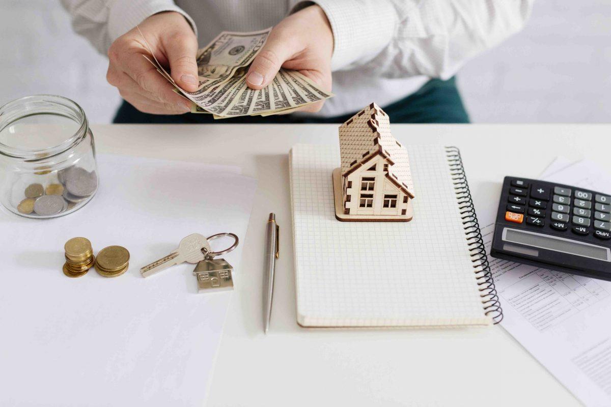 Persona contando dinero con una calculadora y libreta sobre la mesa.