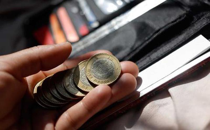 Cartera color negra con algunas tarjetas de crédito y monedas.