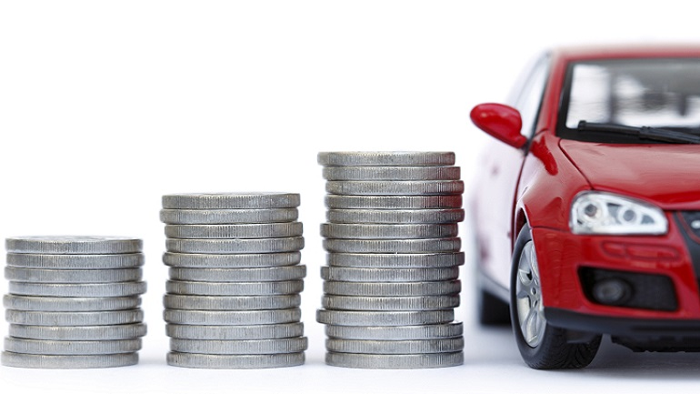 Auto rojo estacionado a lado de una torre de monedas.